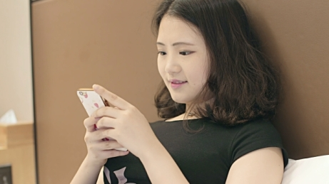 Asian girl sms texting with cellphone - Getty Images